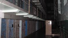 The long tiers of a cellblock at the West Virginia Penitentiary, a retired Gothic-style prison in Moundsville, fade into an eerie shadow. The common shower for inmates is at the left; in the right, steel-walled cells, four tiers high. (Mark Washburn/Charlotte Observer/MCT)