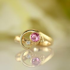 Meet ALVA - one of my most playful and romantic rings which dares to be unashamedly asymmetrical. This version is extra feminine with its pink sapphire and small companion diamond sparkling against the rugged surface of the ring proper. A perfect girl power gold ring - or engagement ring for the daring. Pink Sapphire, Dares, Girl Power, Heart Ring, Gold Rings, Surface, Sparkle, Feminine, Meet