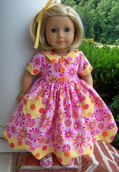 Rainbow Sherbert Dress made in a vintage Daisy Kingdom design! This short sleeve summer dress is made of bright pink cotton. The fully lined bodice has a contrasting yellow polka dot collar, bright orange buttons and sleeves that have matching scalloped cuffs. The very full skirt is decorated with tulip pockets and a contrasting scalloped edging along the hem.