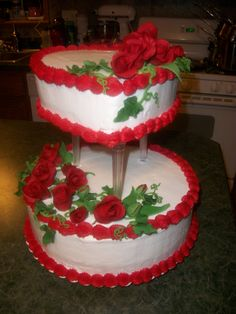 """Red Roses with Dew"" Wedding cake. Sugar roses with vines and greenery, complete with dew drops! The top tier is heart shaped, while the bottom is round."