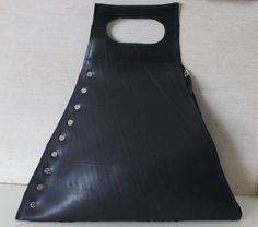 Shaped like a triangle, this elegant and trendy bag is made from 100% recycled inner tube. A zipper on one side and studs along the other, this bag is perfect for any occasion. Stitching available in two different colours: green and black. Styles differ due to tread marks and inside lining. Please inquire within.