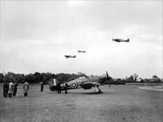 Journalists from Dominions newspapers watch a flight of Hawker Hurricane Mark Is of No. 56 Squadron RAF taking off for a sortie over France from North Weald, Essex. In the foreground another Hurricane Mark I of the Squadron, P2764 'US-P', stands at its dispersal point near the perimeter track on the south-western edge of the airfield.