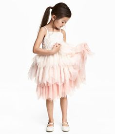 Naturhvid/Lys rosa. Kjole i tyl med smalle skulderstropper. Kjolen er smalt skåret foroven med påsyede pailletter og båndapplikationer. Skåret i taljen med