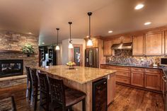 parker co kitchen and fireplace reno, fireplaces mantels, CapStone Home Renovations Parker CO Home kitchen and fireplace remodel with hardwood floors smooth finish walls double sided gas fireplace ledge stone knotty alder cabinets granite countertops new lighting package and slate mosaic tile Doane Designs Andy Gould Photography