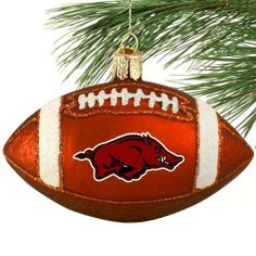 """Arkansas Razorbacks Glass Football Ornament by Football Fanatics. $14.95. Made of glass. Pre-packaged case. Approximately 4"""" in length. Team logo. Glitter accents. Showcase your Arkansas football pride during the holiday season with this 4"""" ornament featuring the team logo and glitter accents! This intricately handcrafted glass ornament was meticulously mouth-blown and hand-painted by skilled artisans using age-old techniques.Made of glassTeam logoGlitter accentsAp..."""