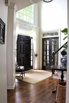 Sidelights and Privacy - curtain panels, gently pulled back along the sidelights, add privacy yet allow light to filter through - via Decorista