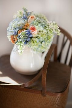 Table pieces in mixed assorted pitchers with shades of ivory flowers and soft pink spray roses