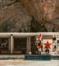 A tourist sitting at a colourful Soviet era bus stop along the Pamir Highway from @goingthewholehogg