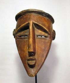Carved wooden mask with wonderful sharp angles and abstract features traditional to Lawalwa masks, from the Congo, Africa. This is a very nice old example with actual field use and wear. The color is a lovely reddish brown, which is likely the red sap of the mukala fruit,and some black natural pigments. a Collector quality mask, one of the finest examples we have handled.