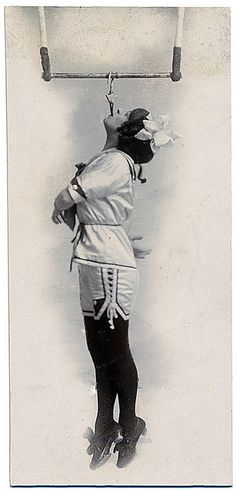 Edwardian era circus performer Pansy Chinery (c. 1916) dangling in the air by her teeth.
