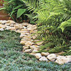 Great idea for grass-free backyard.  Mondo grass, rock border.