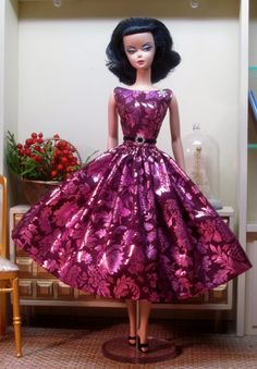 A vibrant metallic tone on tone print in magenta makes up this festive party dress. The dress has a boat necked bodice and a voluminous skirt. A thin black velvet belt with a crystal and silver …