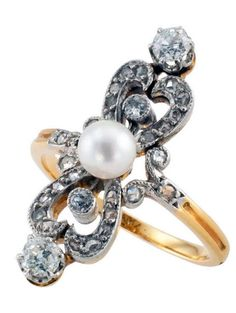 *Edwardian Pearl & Diamond Ring, This French platinum and 18 karat gold ring centers upon a single 5 mm. pearl set between a pair of diamond heart-shaped motifs. Produced by a living sea creature, the pearl represents purity and loyalty, the only gem that requires no polishing or faceting to reveal its natural beauty; diamonds strength and everlasting love.  1910.