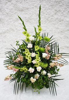A mache arrangement of greens and peach, stunning! - Four Seasons Flowers