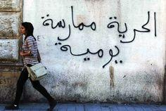 "الحرية ممارسة يومية    Freedom is a daily practice  A Tunisian woman walks past a graffiti which reads, ""Freedom is a daily practice"". Tunisia boasts of some of the most advanced women's rights in the Arab world, 2011.   Photo credit: Anis Mili / Reuters"