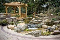 aménagement extérieur avec pergola et étang avec pierres