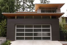 Modern garage door. Cedar soffits. Dark siding.