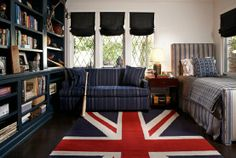 """This transitional room is decidedly masculine with striped upholstered bed and comfy sofa in fabrics that could be a man's suit. The british rug gives this room a bright pop of colour. Black window coverings are balanced and give less """"matchy' than if they were blue.."""