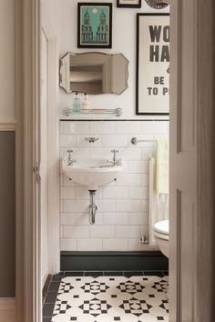 Love the combination of large subway tile with the patterned floor tile with the thick gray baseboard trim in this bathroom