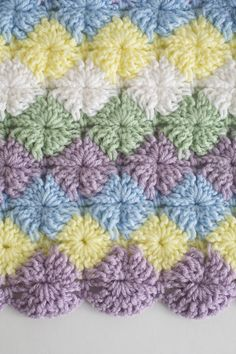 Pastel shades of purple, blue and green are the basis for this soft crochet afghan. Comprised of easy-to-work shell stitches, this throw will give your living room that soft color accent it needs.