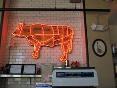 Cool neon sign hanging in a butcher shop.