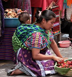 Antigua Guatemala old town market place.  Indian women with traditional costume carrying her baby the old fashion way  Antigua, Guatemala Central America