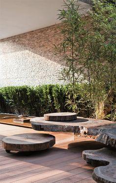 O deque (Woodwi) é sombreado pela pérgula de aço cortén com cobertura de sisal. Bancos de troncos de madeira (Tora Brasil) compõem a área de descanso, escoltada por bambus-da-fortuna.