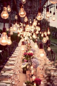 a Beautiful Dinner table lit by hanging rustic light bulbs for a beautiful rustic wedding reception #wedding #photography #reception