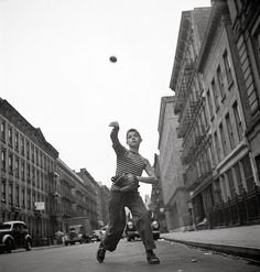 Young boy tossing a ball on a city street, a photo by Cornell Capa, New York City, 1948