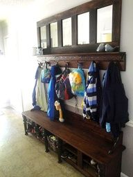 an old church pew is repurposed for the entry. This is accented with the mirror/clothes hook shelf above it. An old door or old windows could be repurposed for the mirror /shelf.