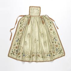 White silk taffeta apron with a small bib and full gathered skirt, embroidered with a deep border and small sprays in field of vines, flowers and grape clusters in many colors. Trimmed with a pink silk galloon; belt and ties of pink silk ribbon.
