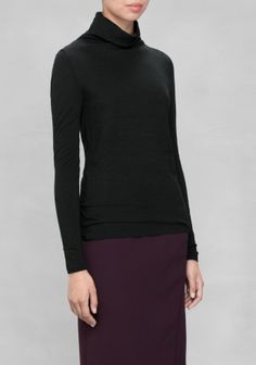 £35 This thin, yet warm wool sweater has a regular fit and features an asymmetric turtleneck that loosely drapes around the neck, providing an elegant and versatile look.