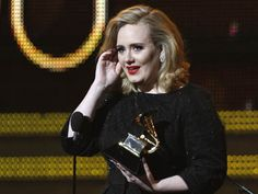 """Singer Adele accepts her award for """"Best Pop Solo Performace"""" at the 54th annual Grammy Awards in Los Angeles."""
