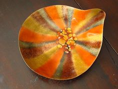 Take a look at this vintage Mid-Centrury Modern dish, ashtray or tip tray from Bovano of Cheshire, Connecticut. The handcrafted enamel on copper has a beautiful warm golden, orange and reddish brown design. The tear drop shaped dish is 7½  inches at it's longest. Very good condition, one tiny crazing area but no breaks or chips. A desirable Eames era piece. Great modern design. Retains it's sticker on the bottom.