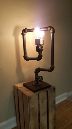 This steampunk pipe lamp features a wooden base, two Edison style bulbs, and a water valve on/off switch. Shipping available.