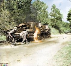 Men of the 26th Battalion, Queen's Royal Regiment (West Surrey), 169th Brigade, advance past a pair of burning German Panzer IV tanks in the Salerno area of Italy.