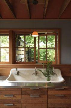 Casement windows, triple sink, stainless steel counter.