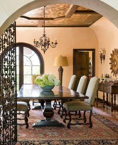 Through an arched opening, the dining room walls are glazed a blushed peach tone under another original stenciled and gilded ceiling. The woodwork is painted a faux grained walnut. The Country Trestle table by Emanuel Morez and the Barcelona dining chairs by Panache Designs are covered in a Kravet fabric.