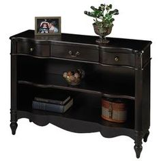 Three-drawer bookcase with brass-finished hardware.Product: BookcaseConstruction Material: Hardwoods and cherry veneersColor: BlackFeatures: Three drawers with antique brass finished hardwareDimensions: 33 H x 42 W x 13 DNote: Some assembly required