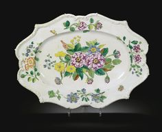 Italian, Doccia factory, circa 1745 DISH of oval silver form with ribbon-tied reeded and scroll moulded rim, painted in the centre with naturalistic brightly coloured flowers, the border painted with four spaced flower sprays and insects porcelain