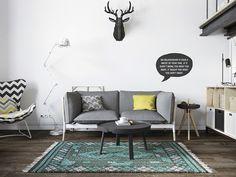 Sala de estar em loft projetado pelo designer Denis Krasikov. Em estilo escandinavo, apresenta uma decoração original, pontuada por cores e com um visual minimalista. O sofá é cinza, o tapete colorido, em um tom mais claro de verde e na parede é possível notal adesivo de vinil que decora com frase divertida