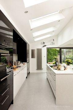 A striking contemporary minimalist kitchen with central island and sleek in design.  The kitchen has an open plan dining area and has a bright sunny aspect owing to its large sky lights and sliding glass doors which open onto the garden.