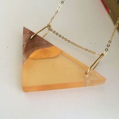 This pendant has been handmade from a piece of burl wood and orange resin. Both resin and wood are smooth to the touch. The triangle pendant measures 2 inches on its longest side (top) It hangs from a