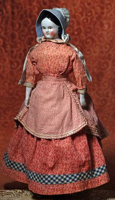 """EARLY GERMAN PORCELAIN DOLL. 20"""". Porcelain shoulderhead, painted and sculpted black """"Covered Wagon"""" hair style, painted features, outlined brown eyes, red and black lid lines, tapered brows, rosy cheeks, closed mouth with upturned corners and slightly smiling expression, cloth body with porcelain lower limbs, painted black shoes with red laces, wears antique cotton print dress, apron, and bonnet. Estimate: $500/600."""