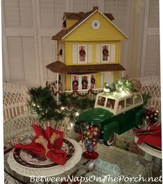 A Christmas table setting featuring a sweet dollhouse and a woody car bringing home the Christmas tree.