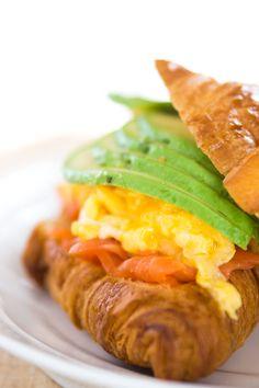 Avocado, Smoked Salmon, and Scrambled Egg Croissant Sandwich.
