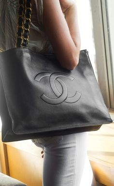 "Leather Tote with double ""C"" and large chain link. Chanel's interlocking C's will never go out of style."