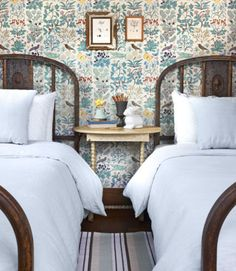 What they saved: The unpainted finish on the wood windows and trim. What they changed: Swapping out the chests and double bed for a pair of vintage iron twin beds and a painted spindle-leg table opens up the tight quarters and offers more flexibility for hosting guests. What they added: Wallpaper inspired by 18th-century botanical prints, which infuses the space with cheerful color and pattern in keeping with styles and motifs that were popular when the house was built. (Apothecary's Garden ...