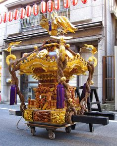 The word mikoshi can be written in two ways as 御輿 (honorable palanquin) or 神輿 (the gods' palanquin). It's an ornate palanquin that's carried on long poles. It usually has a gilded phoenix on top, and it contains a symbol or emblem of the shrine deity.   The shrine's priests ask the kami (gods) to enter the mikoshi, and then the mikoshi is carried around the neighbourhood so that the kami can share their goodwill with all homes and businesses.