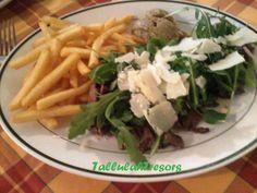 La tagliata con rucola e grana, patatine fritte e polenta